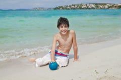 O menino é tem o divertimento na praia Imagem de Stock