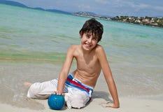 O menino é tem o divertimento na praia Imagens de Stock Royalty Free