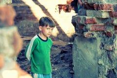 O menino órfão pobre e infeliz, está em uma construção arruinada e olha para fora com perigo Foto encenada imagens de stock royalty free