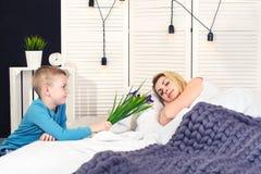 O menino acorda a mamã e dá-lhe um ramalhete das flores na cama Comemorando o dia da mulher Dia do `s da matriz fotografia de stock royalty free