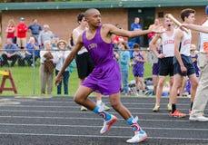 O menino adolescente aceita o bastão na reunião exterior do atletismo foto de stock royalty free