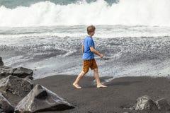 O menino adolescente anda ao longo de uma praia vulcânica preta Fotografia de Stock Royalty Free