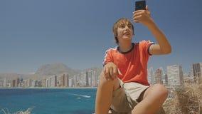 O menino adolescente bonito faz o vídeo chamar ao redor vistas da exibição do smartphone no fundo da skyline da cidade da costa d video estoque