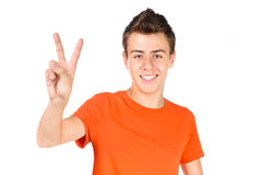 O menino adolescente de sorriso mostra o sinal da vitória Fotografia de Stock