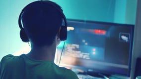 O menino adolescente joga o jogo online no computador através do monitor do Internet nos fones de ouvido o homem do adolescente j video estoque