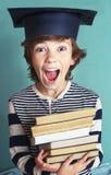 O menino adolescente no chapéu da graduação com pilha registra foto de stock royalty free