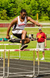 O menino adolescente salta o obstáculo - atletismo - NY imagem de stock