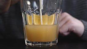 O menino adolescente senta-se em um caf? e bebe-se o suco de laranja de um vidro com uma palha vídeos de arquivo