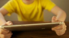 O menino adolescente usa um PC da tabuleta vídeos de arquivo