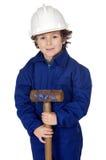 O menino adorável vestiu o trabalhador em um martelo e em um capacete Foto de Stock Royalty Free