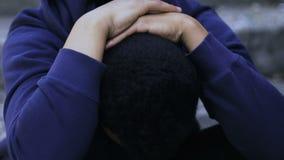 O menino afro-americano comprimido sente só e insolúvel, vítima de bulling, racismo vídeos de arquivo