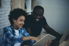 O menino afro-americano mostra a tela da tabuleta para genar fotografia de stock royalty free