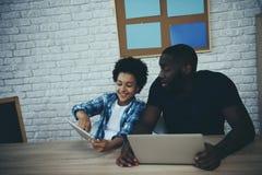 O menino afro-americano mostra a tela da tabuleta para genar imagens de stock