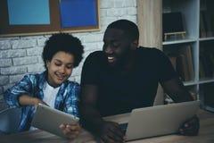 O menino afro-americano mostra a tela da tabuleta para genar fotos de stock royalty free
