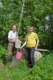 O menino ajuda o pai a derramar a água em uma cubeta Imagens de Stock Royalty Free
