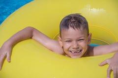 O menino alegre aprecia flutuar no anel inflável na piscina fotografia de stock royalty free