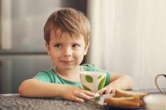 O menino alegre bebe o leite, come o brinde para o café da manhã Imagem de Stock Royalty Free