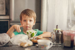 O menino alegre bebe o leite, come o brinde para o café da manhã Imagens de Stock