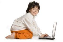 O menino alegre com o portátil no fundo branco imagens de stock