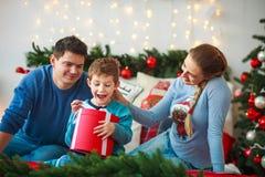 O menino alegre com pais abre a caixa de presente de ano novo na casa do Natal fotos de stock