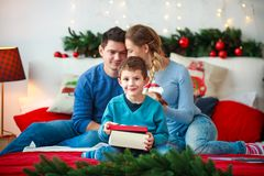 O menino alegre com pais abre a caixa de presente de ano novo na casa do Natal imagens de stock