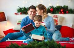 O menino alegre com pais abre uma caixa de presente de ano novo na casa do Natal fotografia de stock royalty free