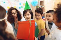 O menino alegre do aniversário no chapéu festivo recebe o presente da menina na festa de anos Fotografia de Stock