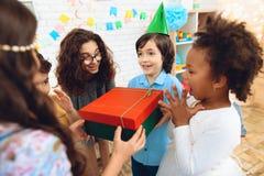 O menino alegre do aniversário no chapéu festivo recebe o presente da menina na festa de anos Fotos de Stock
