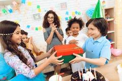 O menino alegre do aniversário no chapéu festivo recebe o presente da menina na imagem da princesa fotografia de stock