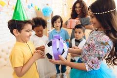 O menino alegre do aniversário recebe a bola do futebol como o presente de aniversário Festa de anos feliz Foto de Stock Royalty Free
