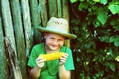 O menino alegre realiza em suas mãos um milho fervido foto de stock royalty free
