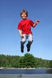 O menino alegre salta no trampoline Imagem de Stock