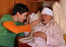 O menino alimenta a mulher doente Fotografia de Stock