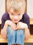 O menino amusing senta-se em uma escada Imagens de Stock