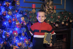 O menino ao lado de uma árvore e de uma chaminé azuis de incandescência de Natal Foto de Stock