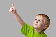 O menino aponta seu dedo para cima Foto de Stock Royalty Free