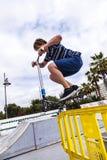 O menino aprecia saltar com seu 'trotinette' do impulso sobre um barriere fotografia de stock