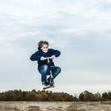 O menino aprecia saltar com seu 'trotinette' sobre uma rampa imagens de stock royalty free