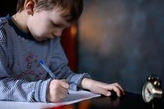 O menino aprende escrever fotografia de stock