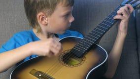 O menino aprende jogar a guitarra que senta-se no sofá Conceito da aprendizagem jogar um instrumento musical vídeos de arquivo