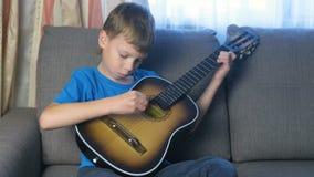 O menino aprende jogar a guitarra que senta-se no sofá Conceito da aprendizagem jogar um instrumento musical video estoque