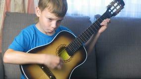 O menino aprende jogar a guitarra que senta-se no sofá Conceito da aprendizagem jogar um instrumento musical filme