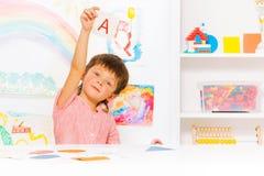 O menino aprende ler mostrar o cartão de letra Fotografia de Stock Royalty Free