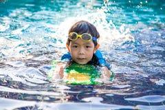 O menino aprende nadar na piscina imagem de stock