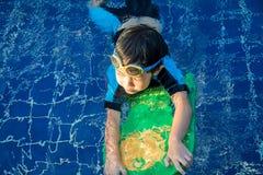 O menino aprende nadar na piscina fotografia de stock royalty free