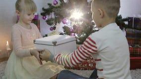 O menino apresenta a menina um presente de Natal filme