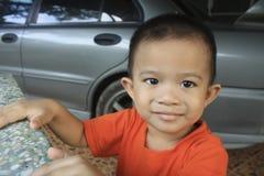 O menino asiático bonito pequeno, faz algo suspeito Fotos de Stock Royalty Free