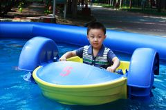O menino asiático está conduzindo o barco Imagem de Stock Royalty Free