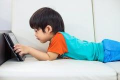 O menino asiático está jogando uma tabuleta em um sofá Foto de Stock