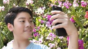 O menino asiático feliz da criança toma uma foto com a flor bonita da orquídea no jardim filme